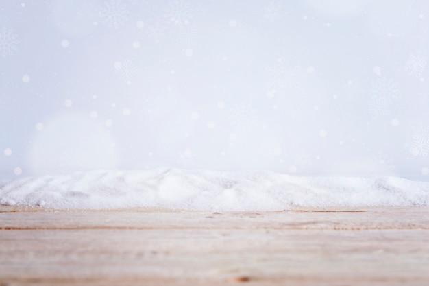 Planche de bois près de tas de neige et de flocons de neige qui tombent Photo gratuit
