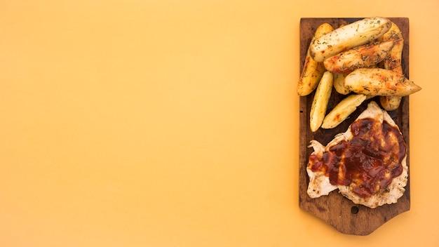 Planche de bois avec des quartiers de pomme de terre et de la viande grillée Photo gratuit