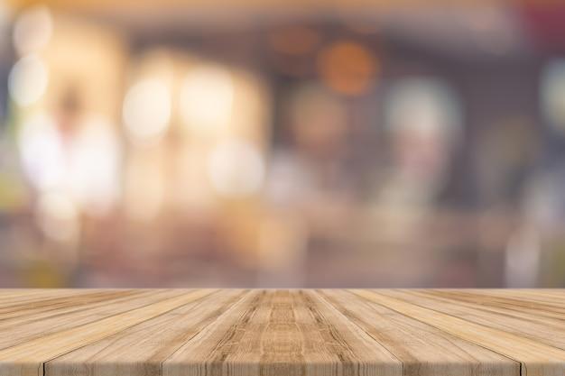 Planche de bois vider la table devant au restaurant arrière-plan flou. Photo Premium