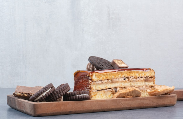 Une Planche à Découper En Bois De Biscuits Et Morceau De Gâteau. Photo gratuit