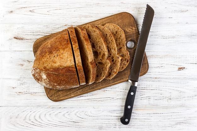 Planche à découper en bois avec du pain blanc en tranches et un couteau sur une table en bois Photo Premium