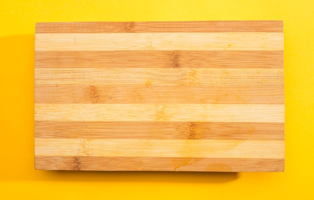 Planche à découper en bois sur fond jaune Photo gratuit