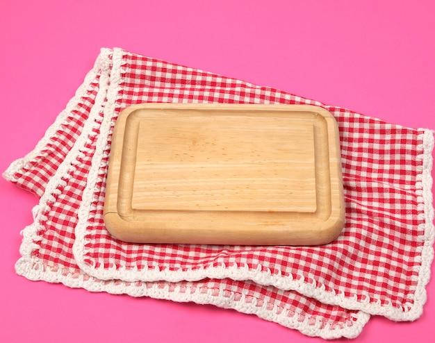 Planche à découper en bois de petite cuisine et serviette de cuisine à carreaux rouges blancs Photo Premium