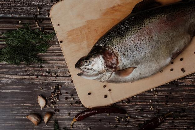 Planche à découper en bois de poisson rouge. truite Photo Premium