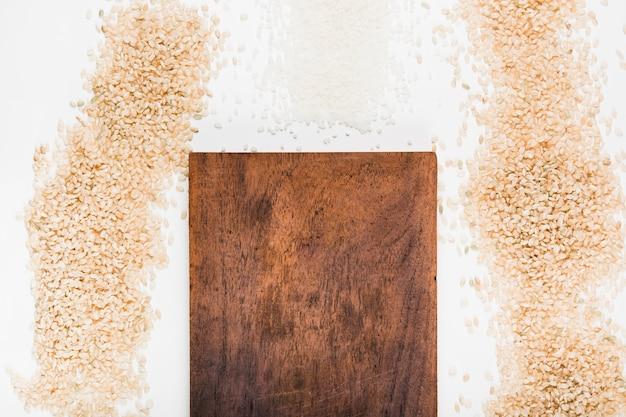 Planche à découper en bois avec une variété de riz non cuit sur fond blanc Photo gratuit