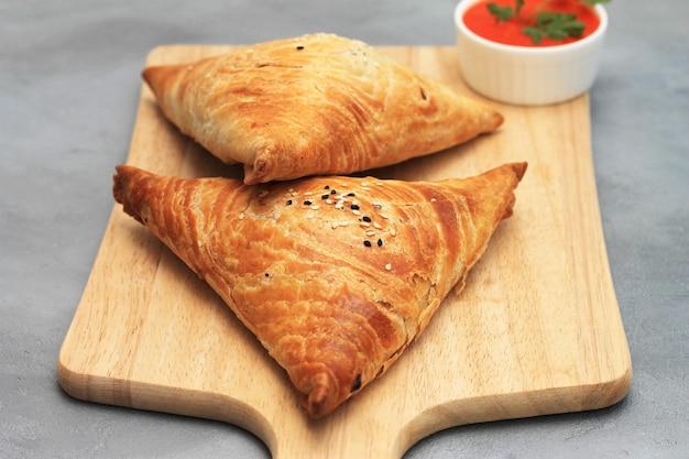 Planche à découper avec de délicieux samosas à la viande et sauce rouge sur fond gris Photo Premium