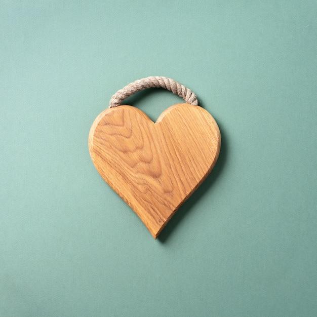 Planche à découper sur fond bleu et vert en forme de coeur. Photo Premium