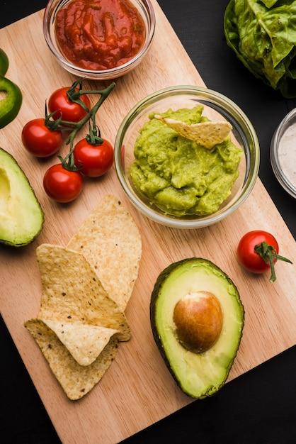 Planche à découper avec des légumes et des sauces Photo gratuit