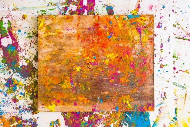 Planche à découper près de taches de différentes couleurs vives et sèches Photo gratuit
