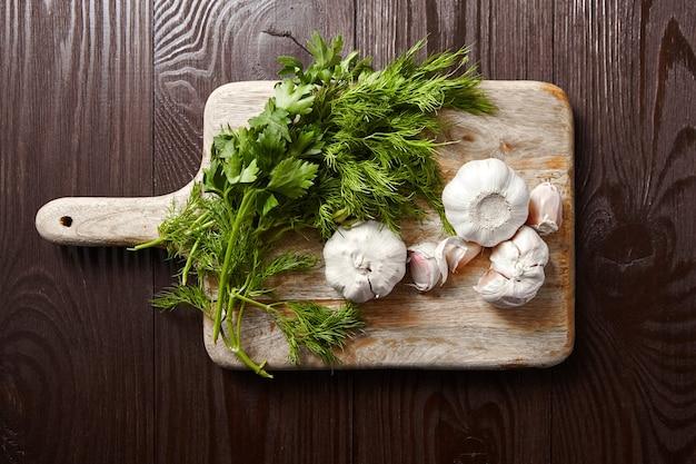 Planche à Découper Avec Têtes Et Gousses D'ail Frais, Bouquet D'aneth Vert Et Persil. Condiments, Vue De Dessus Photo Premium