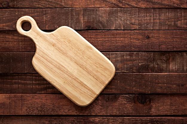 Planche à découper sur une vieille table en bois sombre Photo Premium