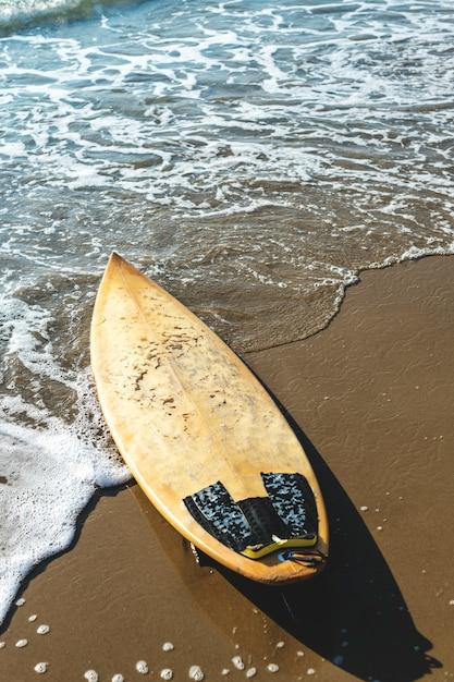 Planche de surf sur une plage de sable Photo gratuit