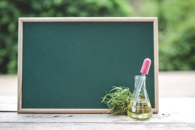 Sur le plancher de bois, il y a de l'huile de chanvre, une feuille de chanvre et le tableau vert est vide pour mettre du texte. Photo gratuit
