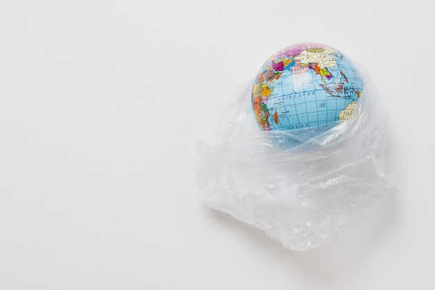 Planète dans un sac en plastique sur fond gris Photo gratuit