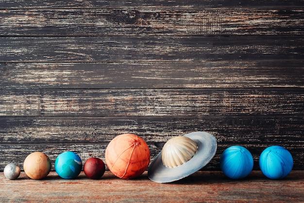 Planètes du système solaire sur fond en bois avec espace de copie Photo Premium