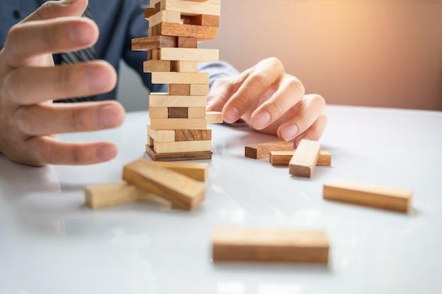 Planification, risque et stratégie dans les affaires, jeux d'argent des hommes placant un bloc en bois sur une tour Photo gratuit