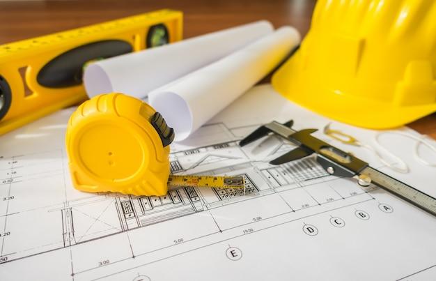 Les plans de construction avec casque jaune et des outils de dessin sur bluep Photo gratuit