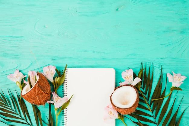 Plante feuilles près de noix de coco avec fleurs et cahier Photo gratuit