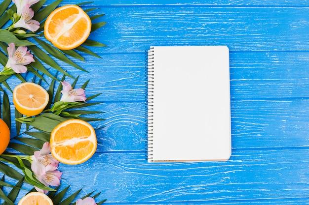 Plante feuilles près des oranges avec des fleurs et un cahier Photo gratuit