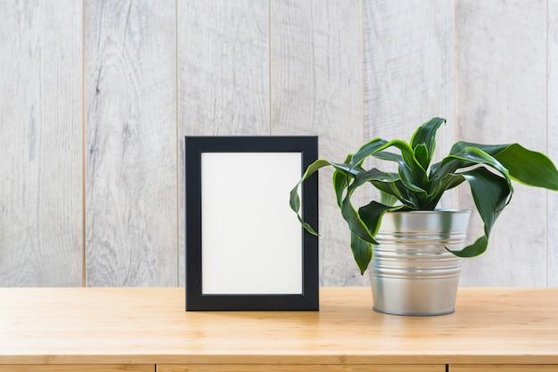 Plante d'intérieur fraîche et cadre photo sur le bureau en bois Photo gratuit
