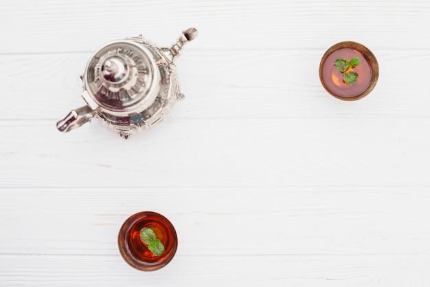 Plantes dans des tasses de thé près de bouilloire vintage Photo gratuit