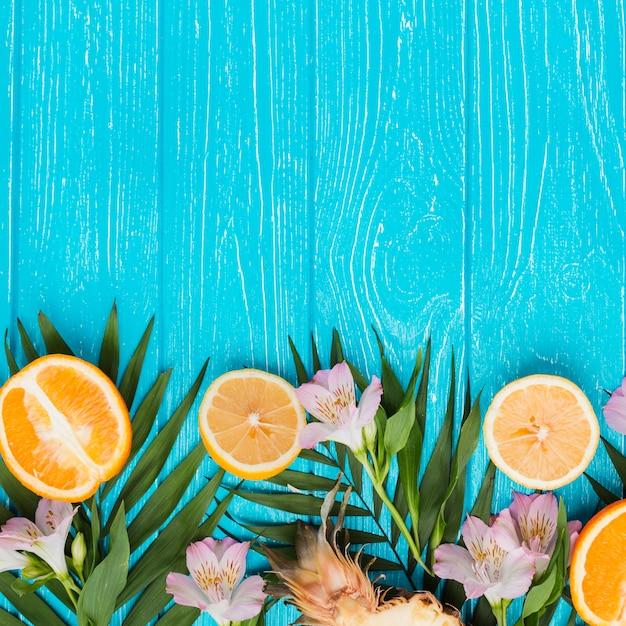 Plantez des feuilles et des fruits exotiques près des fleurs fraîches Photo gratuit