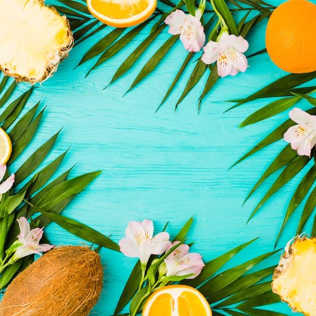 Plantez des feuilles et des fruits exotiques près des fleurs Photo gratuit