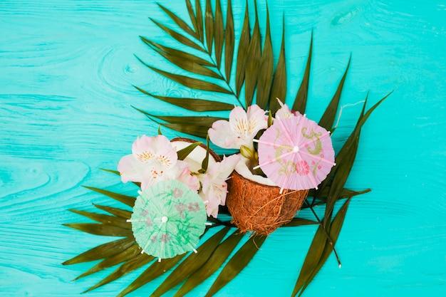 Plantez des feuilles et des noix de coco près des fleurs et des parapluies décoratifs Photo gratuit