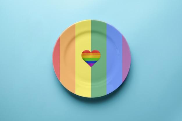 Plaque aux couleurs du drapeau lgbt. notion de drapeau de la fierté fête romantique du festival lgbt. rendez-vous au café avec des lesbiennes, des gays, des bisexuels ou des transgenres solitaires. Photo Premium