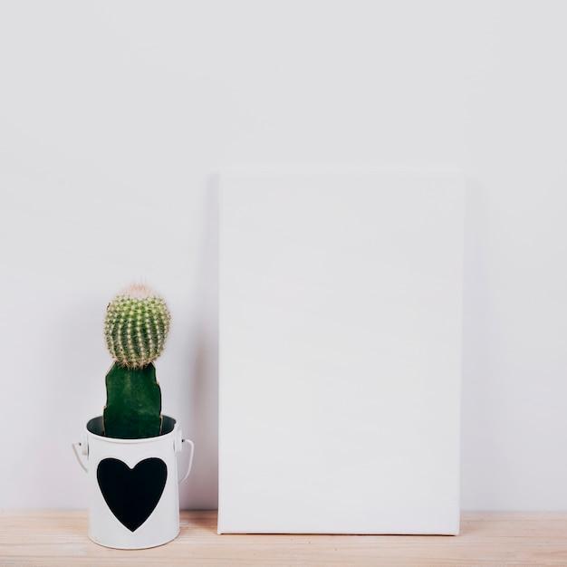 Plaque noire avec une plante succulente à cœur en forme de pot Photo gratuit