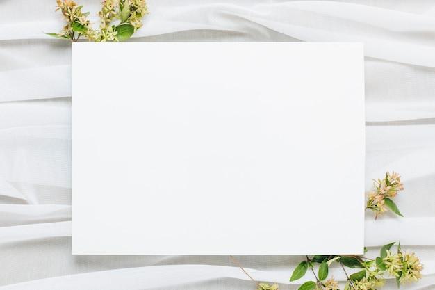 Plaque vierge blanche avec des fleurs sur le foulard Photo gratuit
