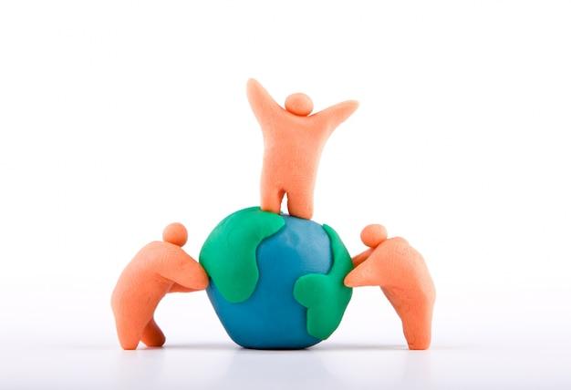 Plasticine des personnes adhérant à la terre Photo gratuit
