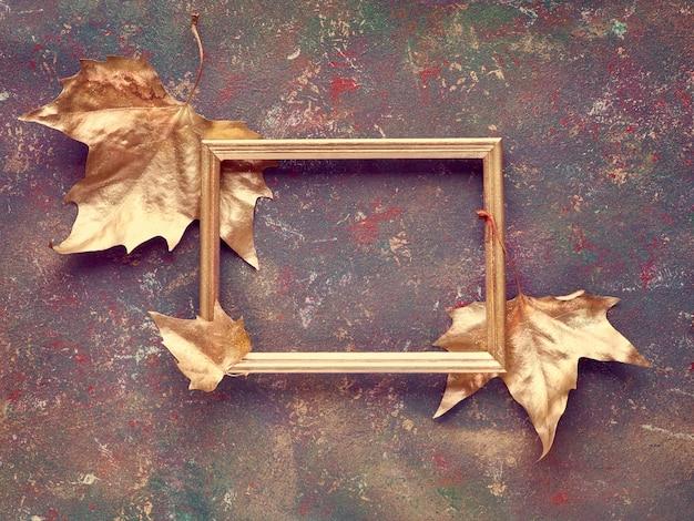 Plat à L'automne Avec Des Feuilles De Sycomore Peint En Or Et Copie-espace Dans Un Cadre Doré Sur Toile Texturée Sombre Photo Premium