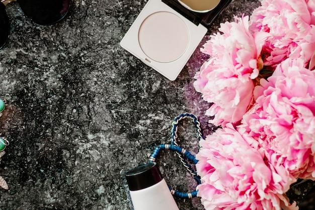 Plat de beauté avec accessoires, parfums, cosmétiques et pivoines sur fond de marbre foncé Photo Premium