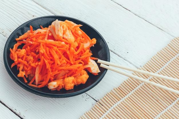 Plat coréen de carottes et de poisson rouge et baguettes sur un fond en bois blanc Photo Premium