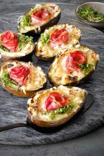 Plat diététique keto: barques à l'avocat avec bacon croquant, fromage fondu et germes de cresson à l'obscurité Photo Premium