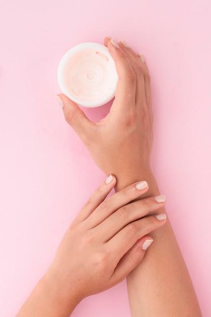 Plat Laïque Femme Tenant Une Boîte De Crème Pour Le Visage Photo gratuit