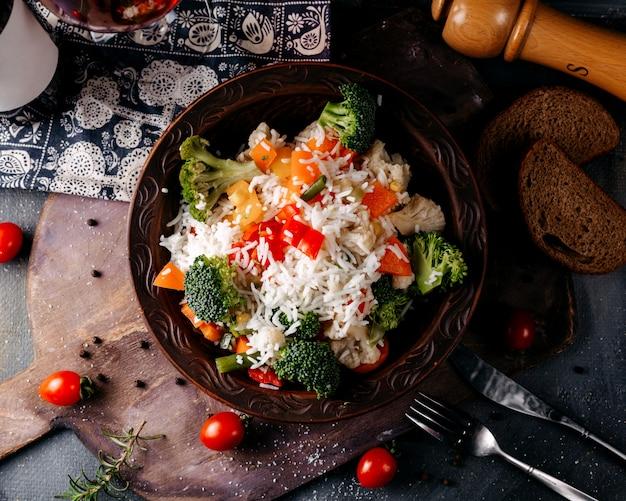 Plat De Légumes Vue De Dessus, Y Compris Les Tomates Rouges Au Brocoli Et Le Riz Sur Le Sol Gris Photo gratuit