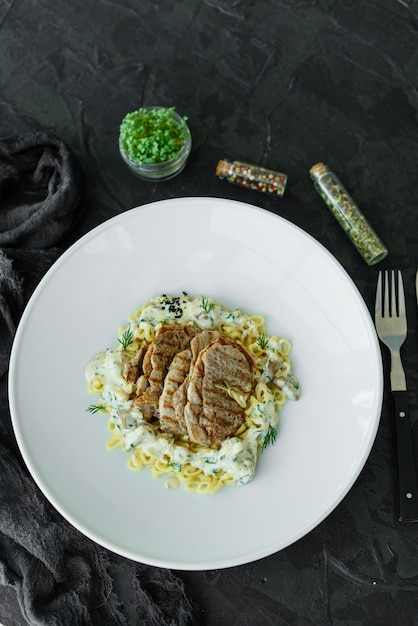Plat avec des morceaux de viande, pâtes, légumes verts, sauce d'un foie gras et de la terre d'olive Photo Premium