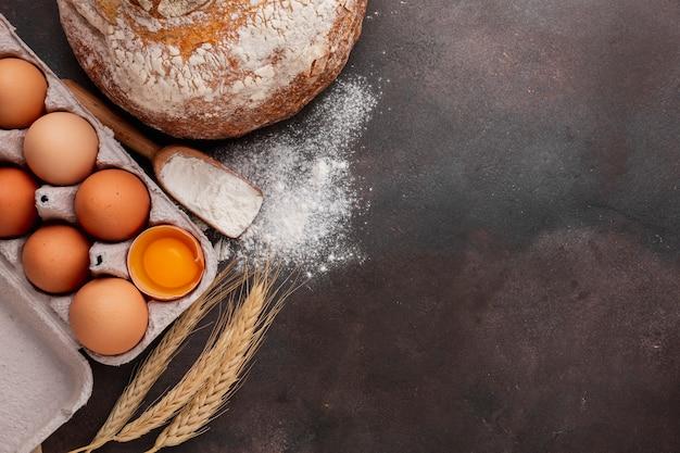 Plat pose de carton d'oeufs avec du pain et de la farine Photo gratuit