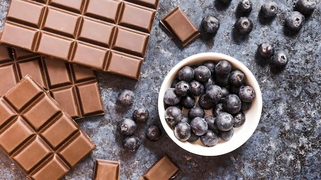 Plat poser chocolat et bleuets sur la table de grunge Photo gratuit