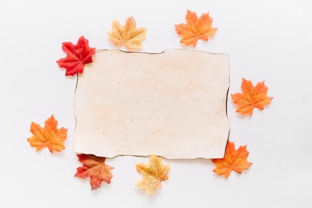 Plat poser de feuille de papier avec des feuilles d'automne autour Photo gratuit
