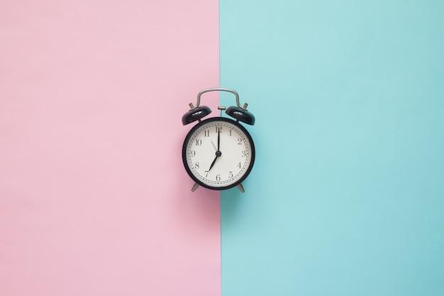Plat poser horloge sur fond rose et bleu Photo Premium