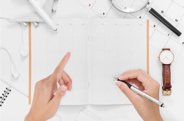 Plat poser des mains de femme écrivant sur le plan d'itinéraire de voyage avec espace Photo Premium