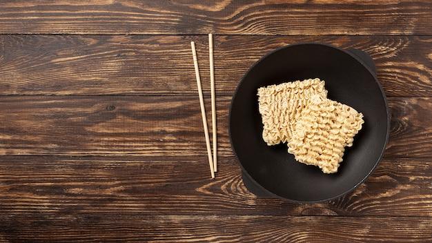 Plat poser nouilles non cuites sur assiette et baguettes avec espace de copie Photo gratuit