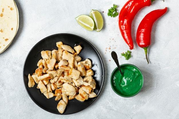 Plat de poulet près de poivrons, sauce verte et citron vert Photo gratuit