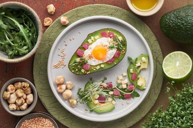 Plat de régime keto: bateau à l'avocat cuit au four avec cubes de jambon, œuf de caille et Photo Premium