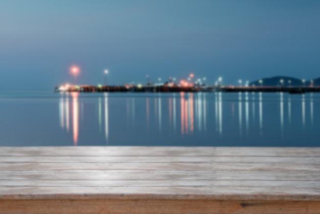 Plateau en bois avec fond de coucher de soleil flou sur la mer, effet de filtre rétro Photo Premium