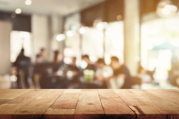 Plateau en bois avec intérieur café flou et personnages en arrière-plan Photo Premium
