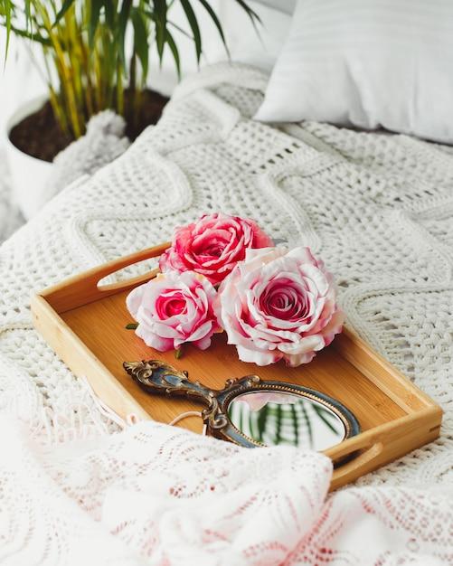 Plateau En Bois Avec Miroir Et Roses Roses Sur Une Couverture Tricotée Photo gratuit